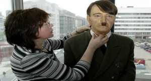An employee prepares a wax figure of Nazi dictator Adolf Hitler for an exhibition next to Berlin's famous former Allied Checkpoint Charlie March 16, 2004. The exhibition features wax figures of famous historical and contemporary personalities. - RTXMH7R